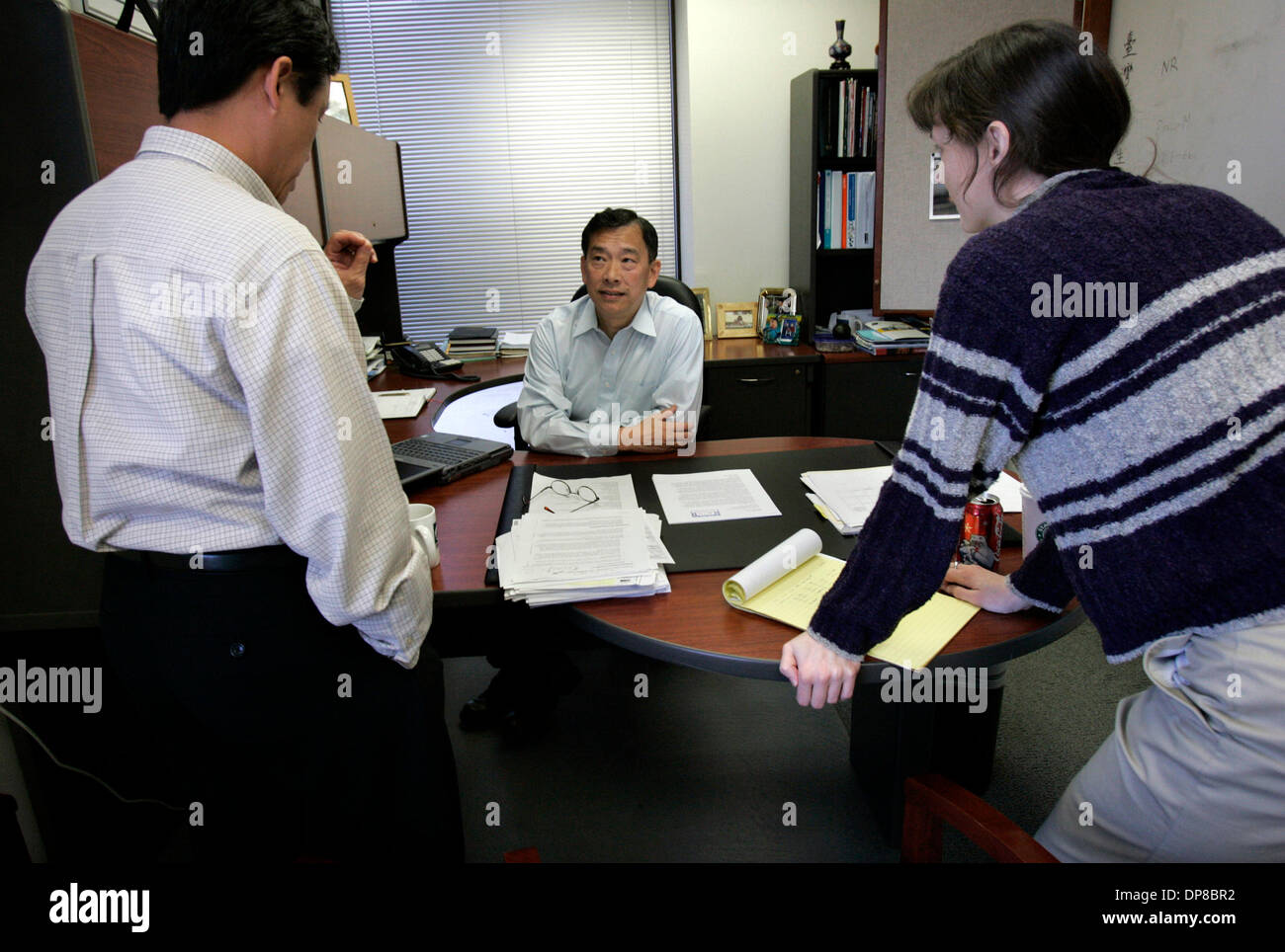 (Published 5/16/2006, C-4)  LE_chang253070x001_3-2-2006_Sorrento Valley_MICHAEL CHANG, CEO of Optimer Pharmaceuticals, Inc.,  in Sorrento Valley, center, talks to YOUE-KONG SHUE, vice-president of clinical development, left, and PAMELA SEARS, senior director, biology, right, about an ongoing project, in his office._LAURA EMBRY/San Diego Union-Tribune - Stock Image