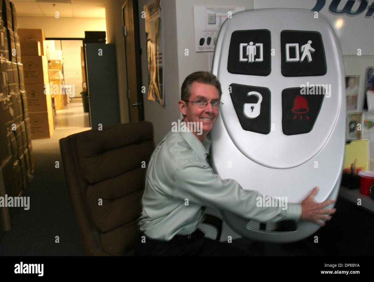 (Published 2/21/2005, E-1) Bob Burns, president of Advanced Bridging Technologies hugs a key fob that is a giant prototype for an instrument that ABT makes, an instrument that allows iPod owners to plug into a wireless system that can be heard over their stereo system.  UT/John Gastaldo - Stock Image