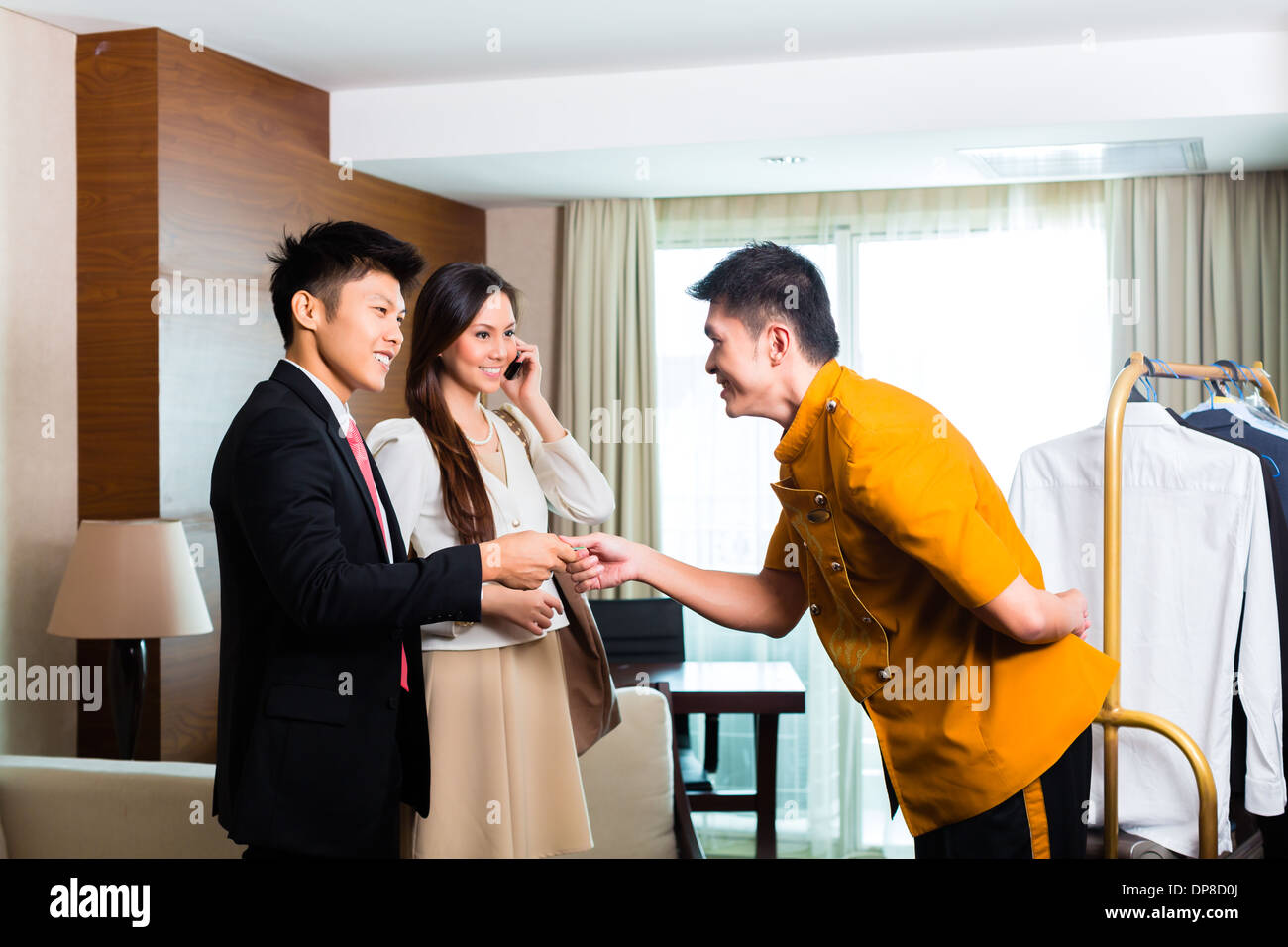 Baggage porter or bellboy or page receiving tip for delivering the suitcase of guests to the hotel room or suite - Stock Image