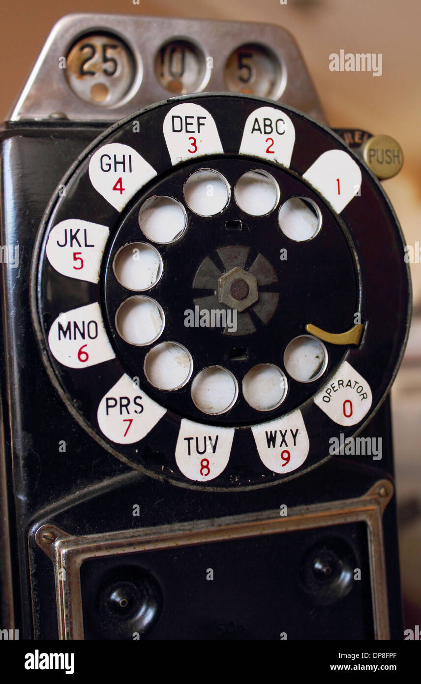 Close up image of an antique rotary pay phone isolated on a white background.Stock Photo