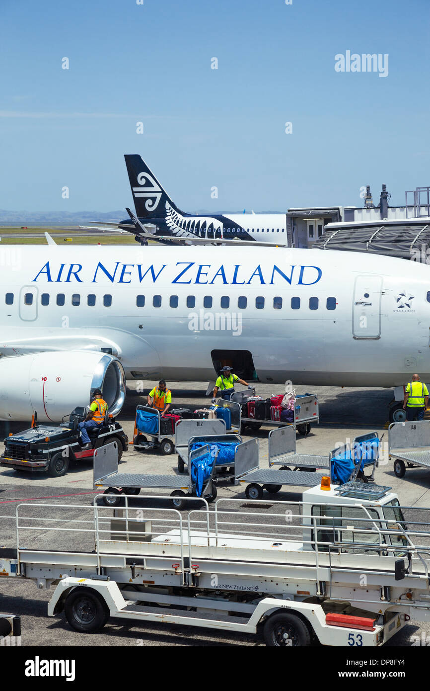 Baggage handlers loading suitcases onto an Air New Zealand aircraft at Auckland airport. North Island, New Zealand. - Stock Image