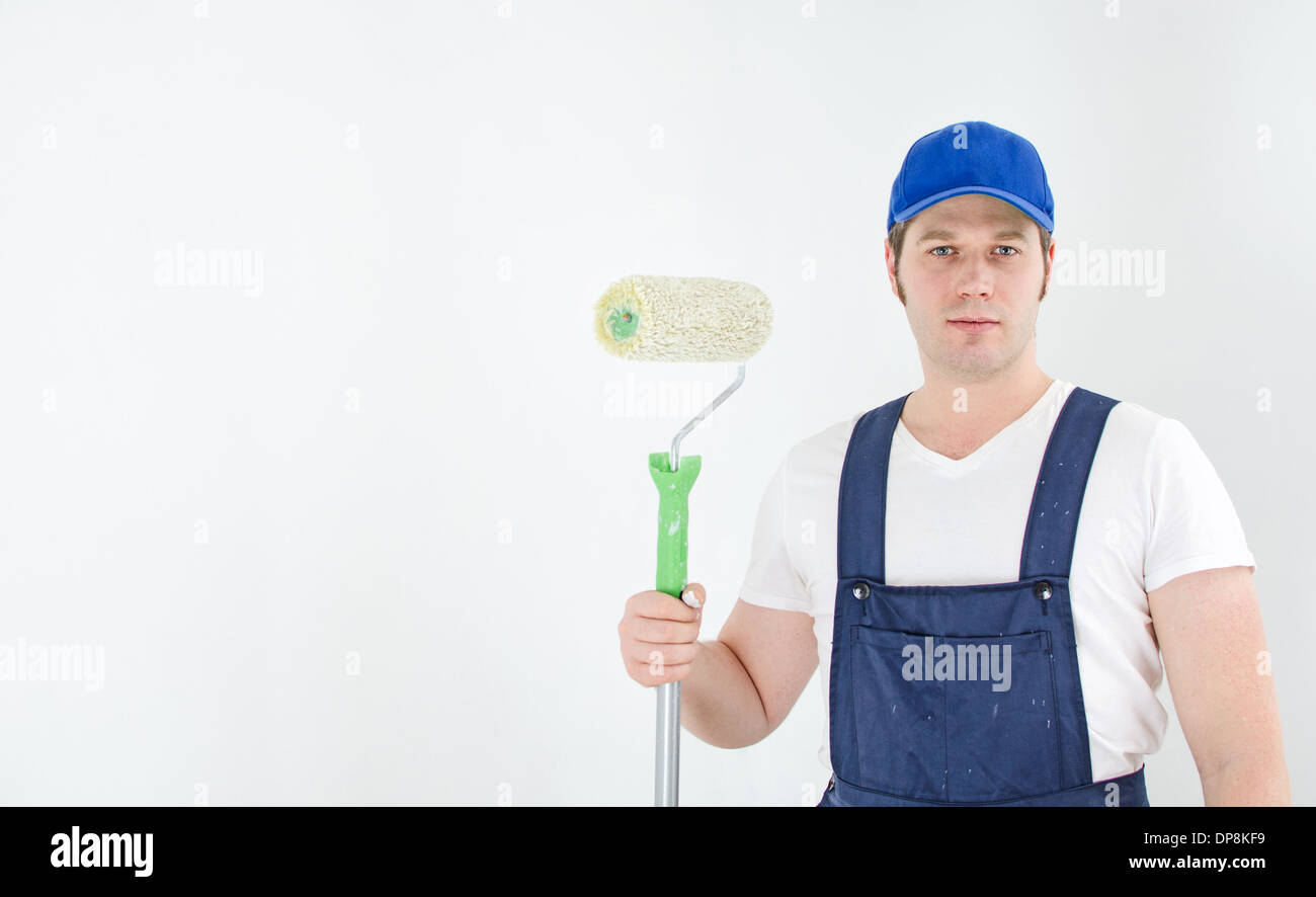 Painter in uniform paints the wall. Space for your text. - Stock Image