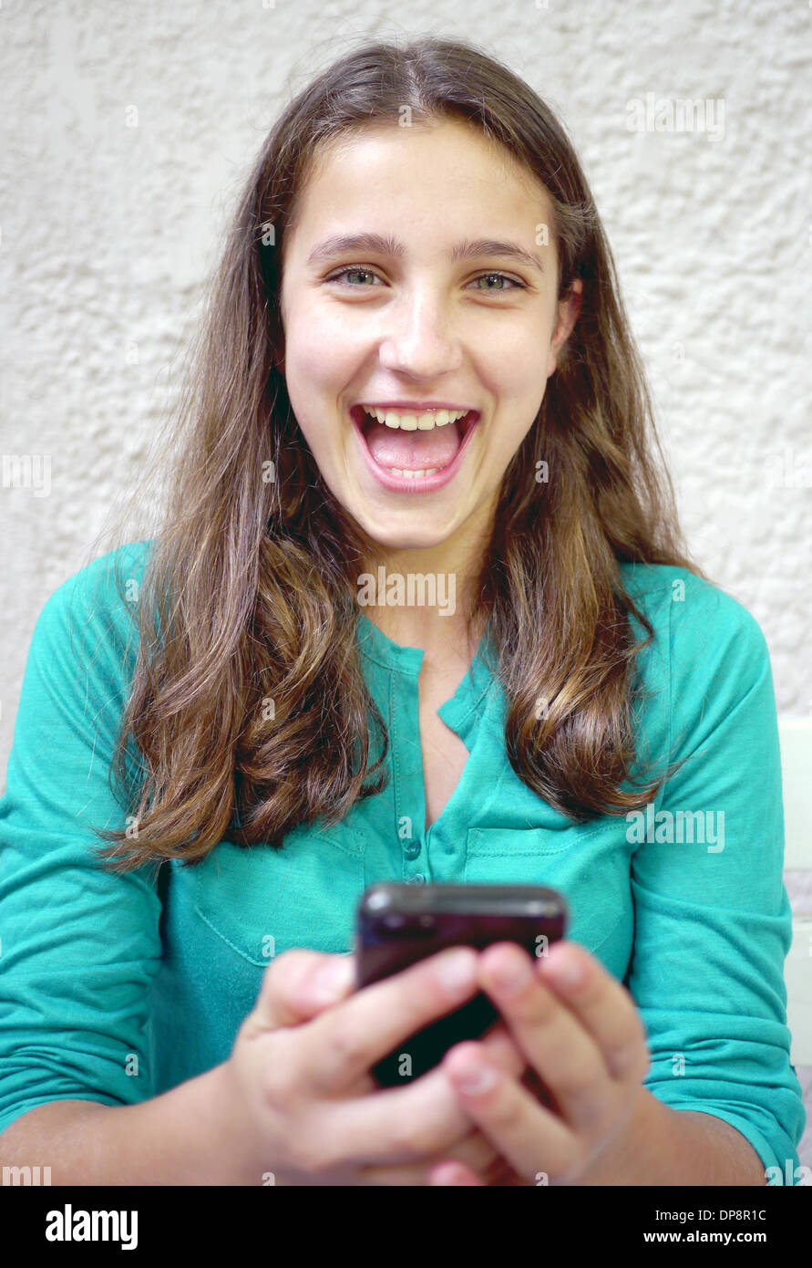 girls laughs at cellphone message - Stock Image