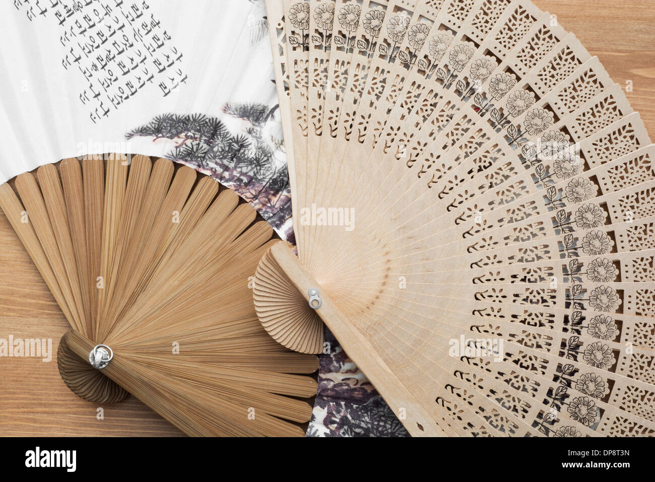 Traditional fans with far eastern motive on a wooden background. - Stock Image