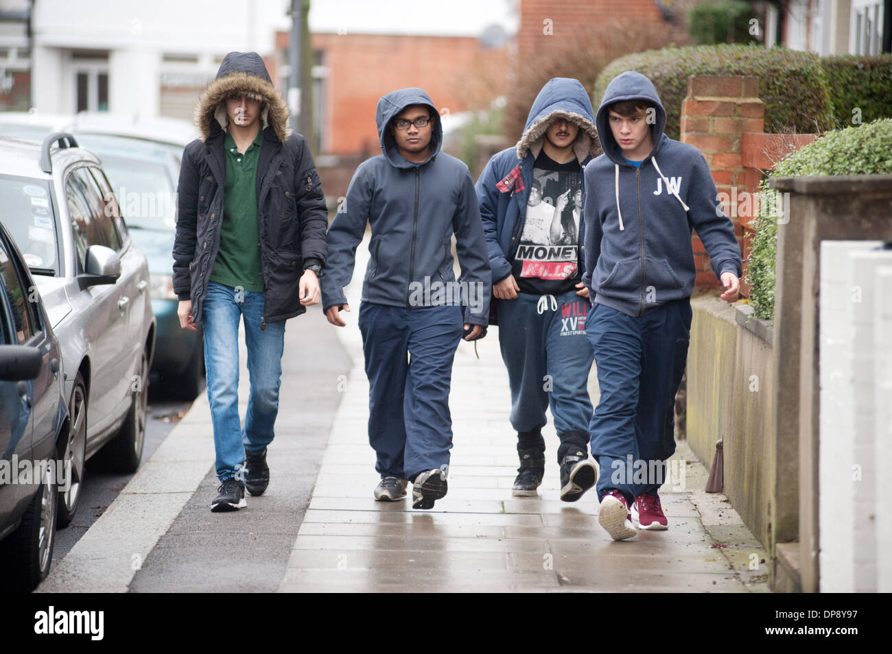 A Group Of Teenage Boys In Hoodies Walking Together Down A