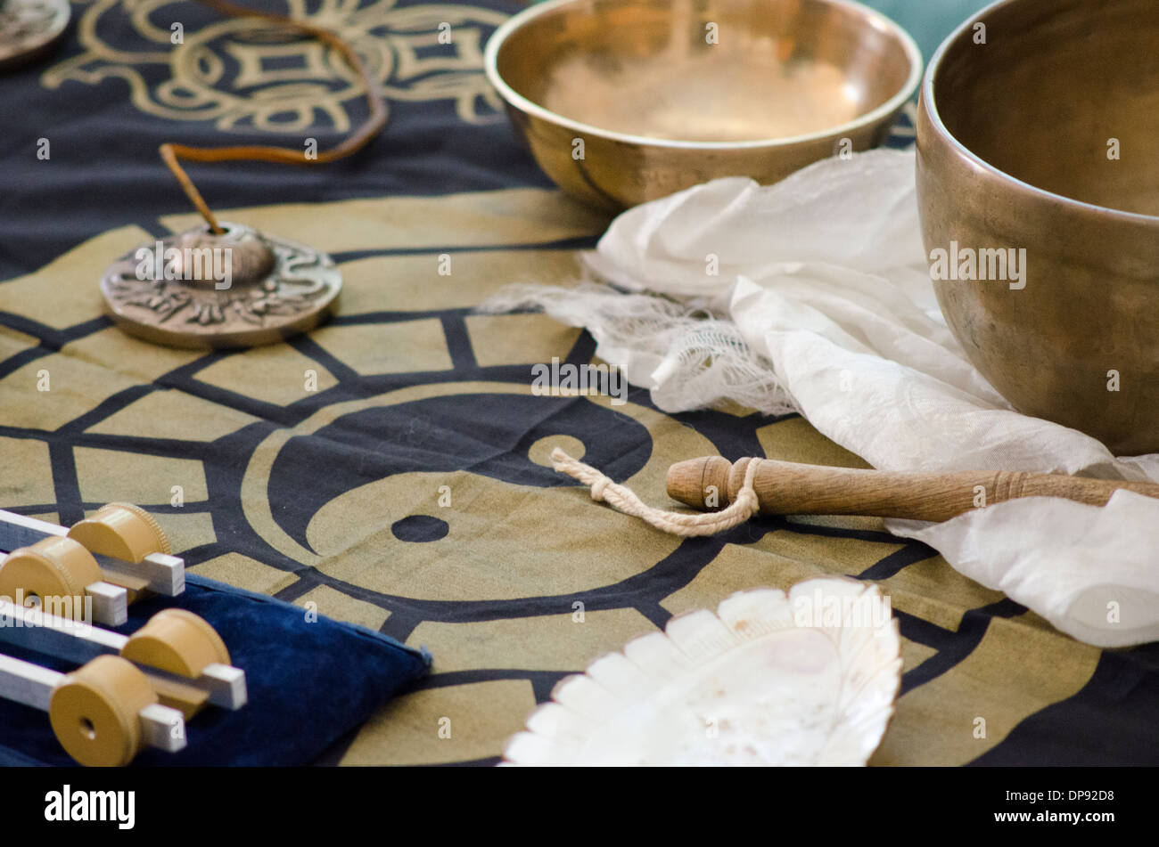 A table-top arrangement around a ying yang of tibetan healing instruments used for holistic healing. - Stock Image