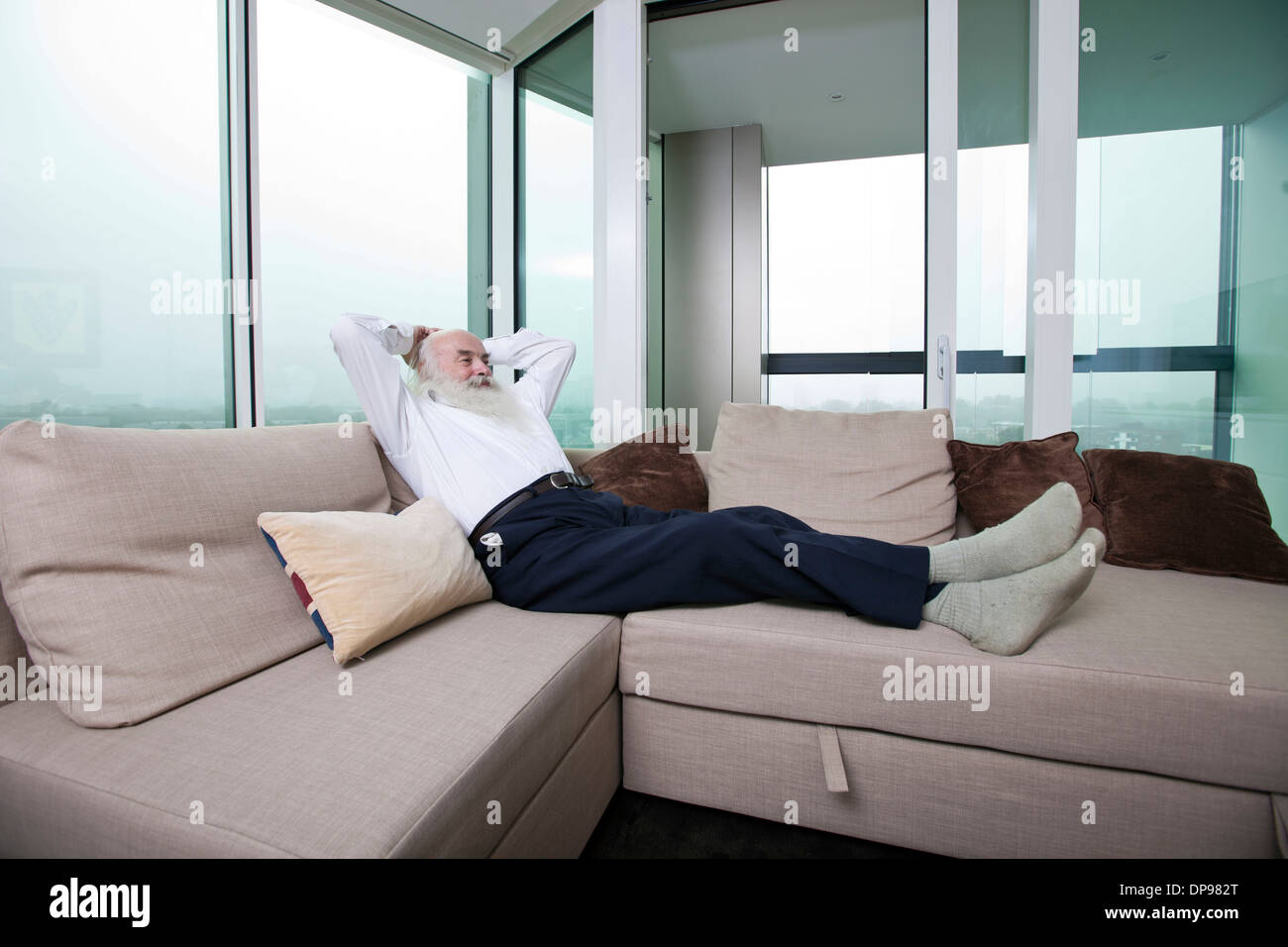 Full length of senior man relaxing on sofa with hands behind head at home - Stock Image