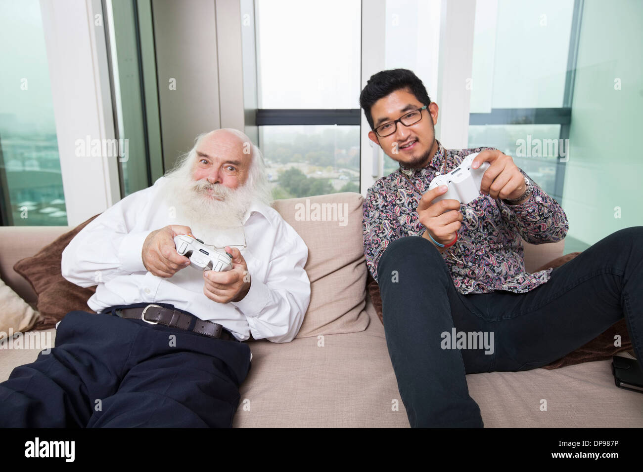 Portrait of grandson playing video game on sofa at home Stock Photo