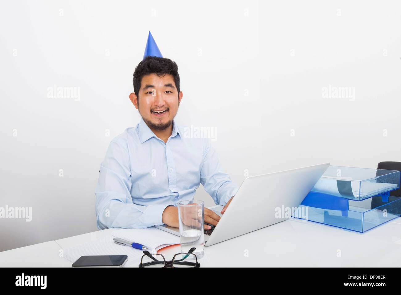 Portrait of happy businessman wearing party hat sitting at desk in office Stock Photo