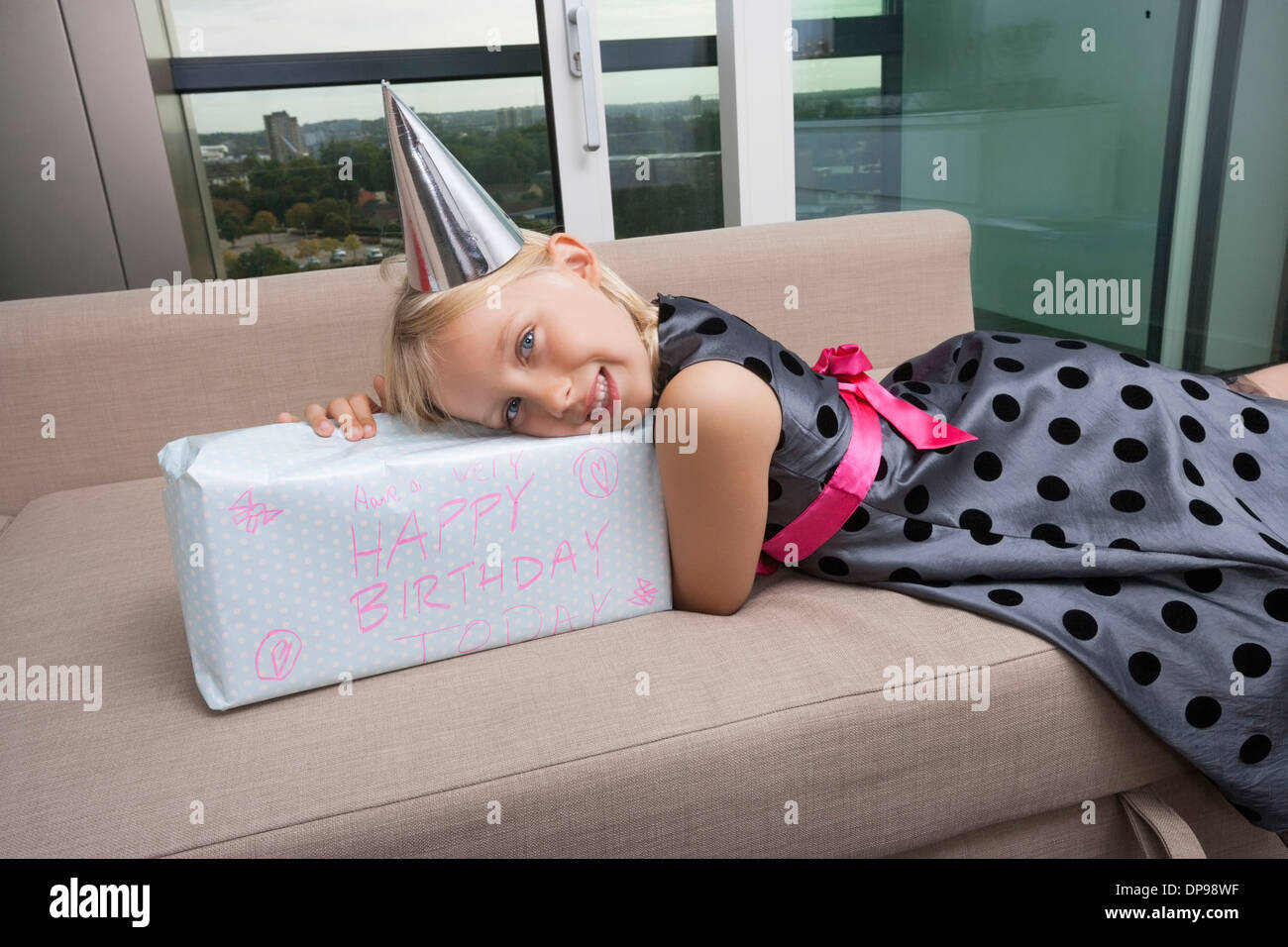 Portrait of girl with birthday gift lying on sofa at home - Stock Image
