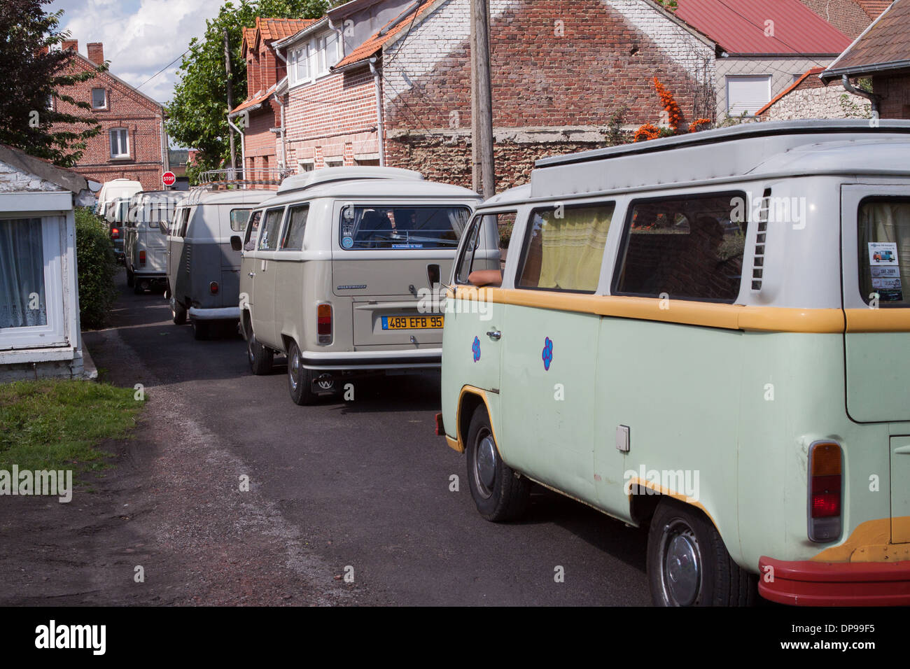 VW Campervans drive through a street in France - Stock Image