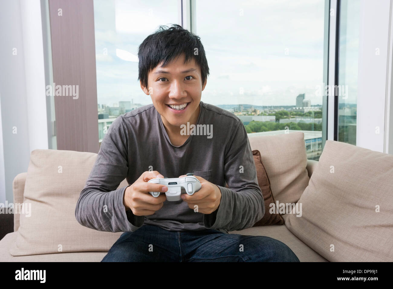Excited mid adult man playing video game on sofa - Stock Image