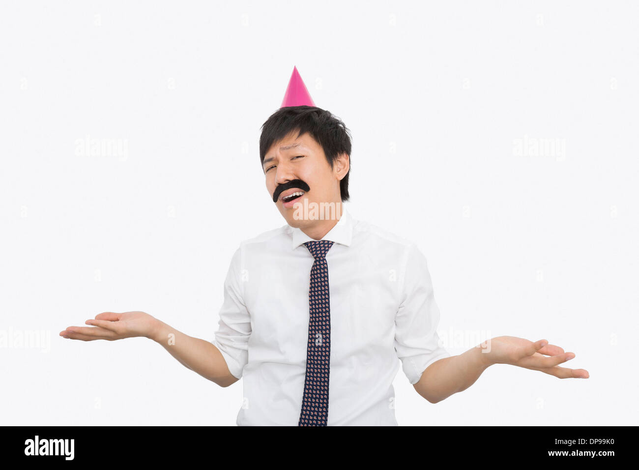 Mid adult businessman shrugging his shoulders over white background - Stock Image