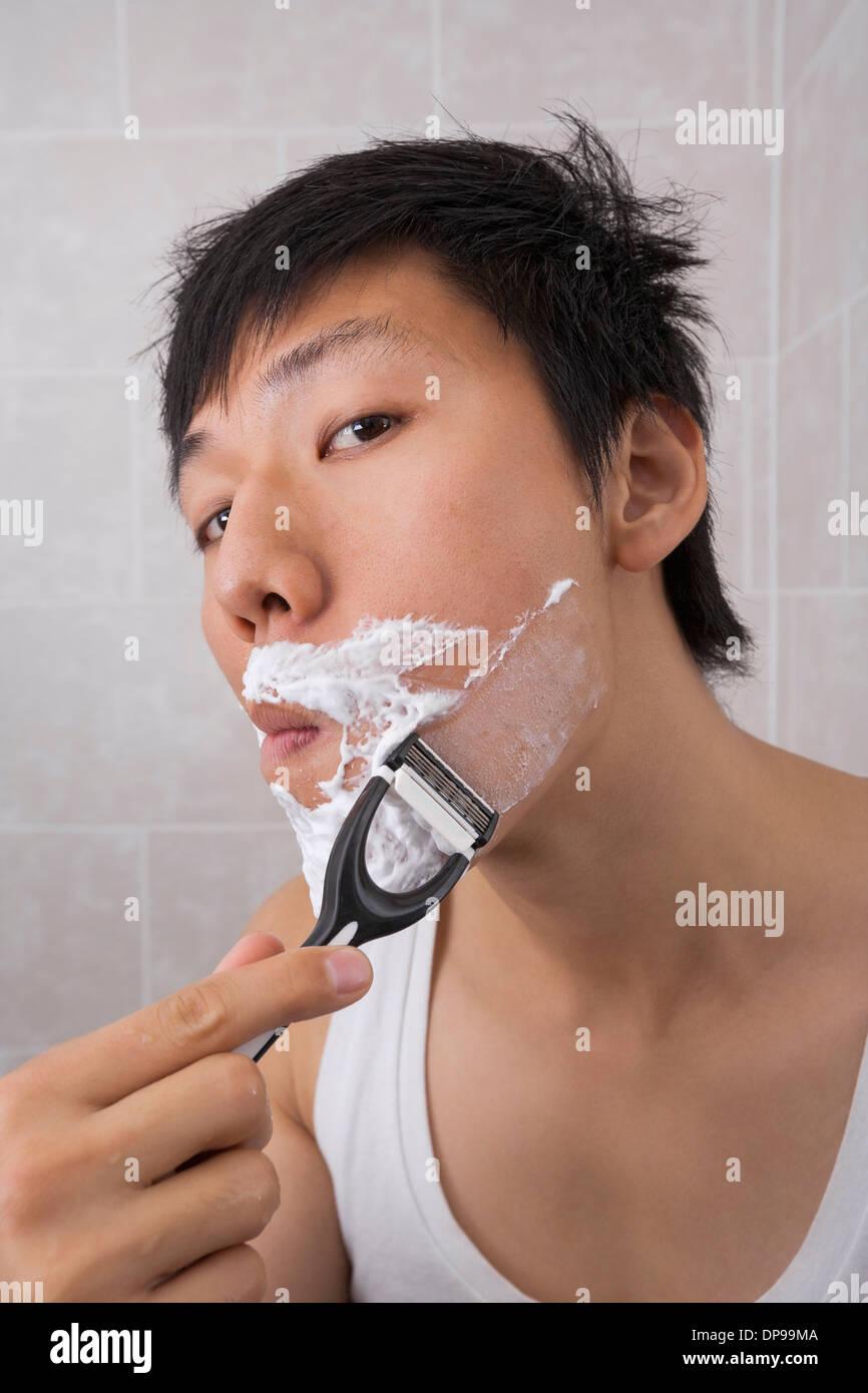Portrait of mid adult Asian man shaving in bathroom - Stock Image