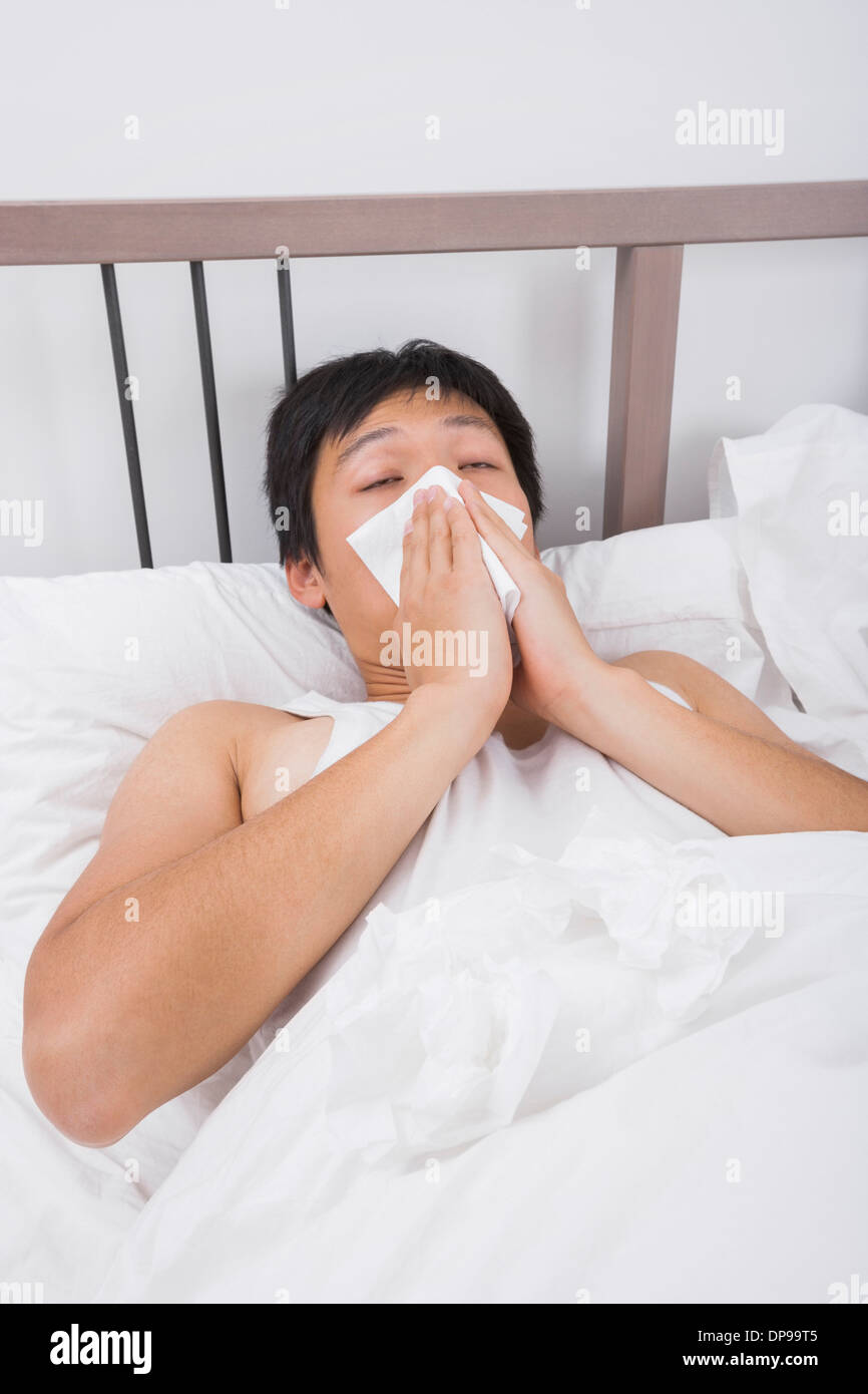 Asian man blowing nose in bed - Stock Image
