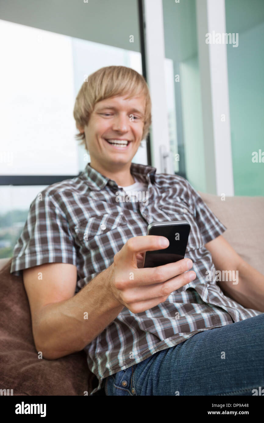 Cheerful mid-adult man text messaging on sofa at home Stock Photo