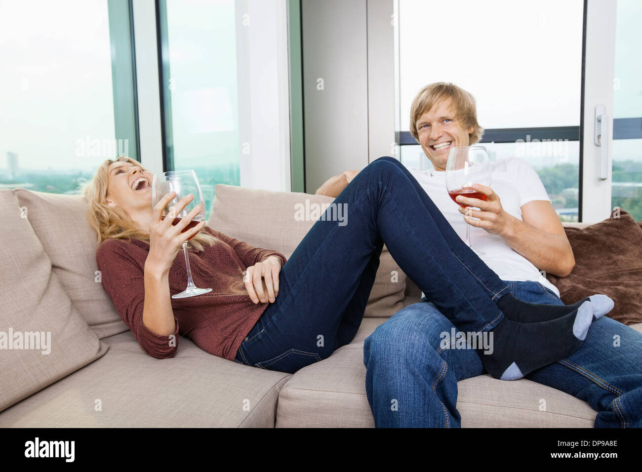 Cheerful relaxed couple with wine glasses in living room at home - Stock Image