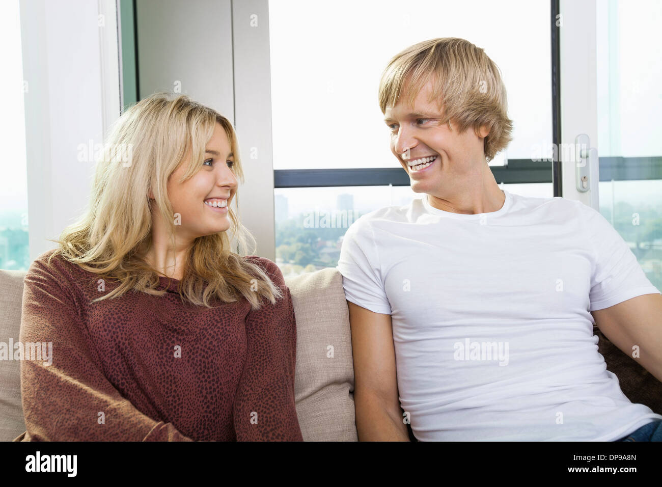 Cheerful couple sitting on sofa and looking at each other at home - Stock Image