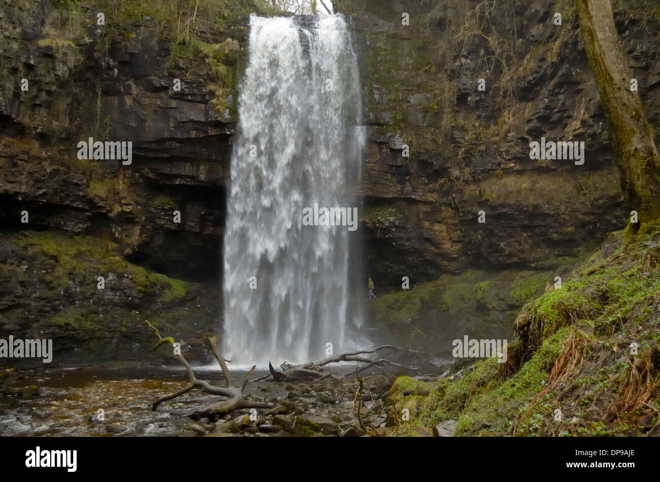 Henrhyd Falls with person walking behind the curtain - Stock Image