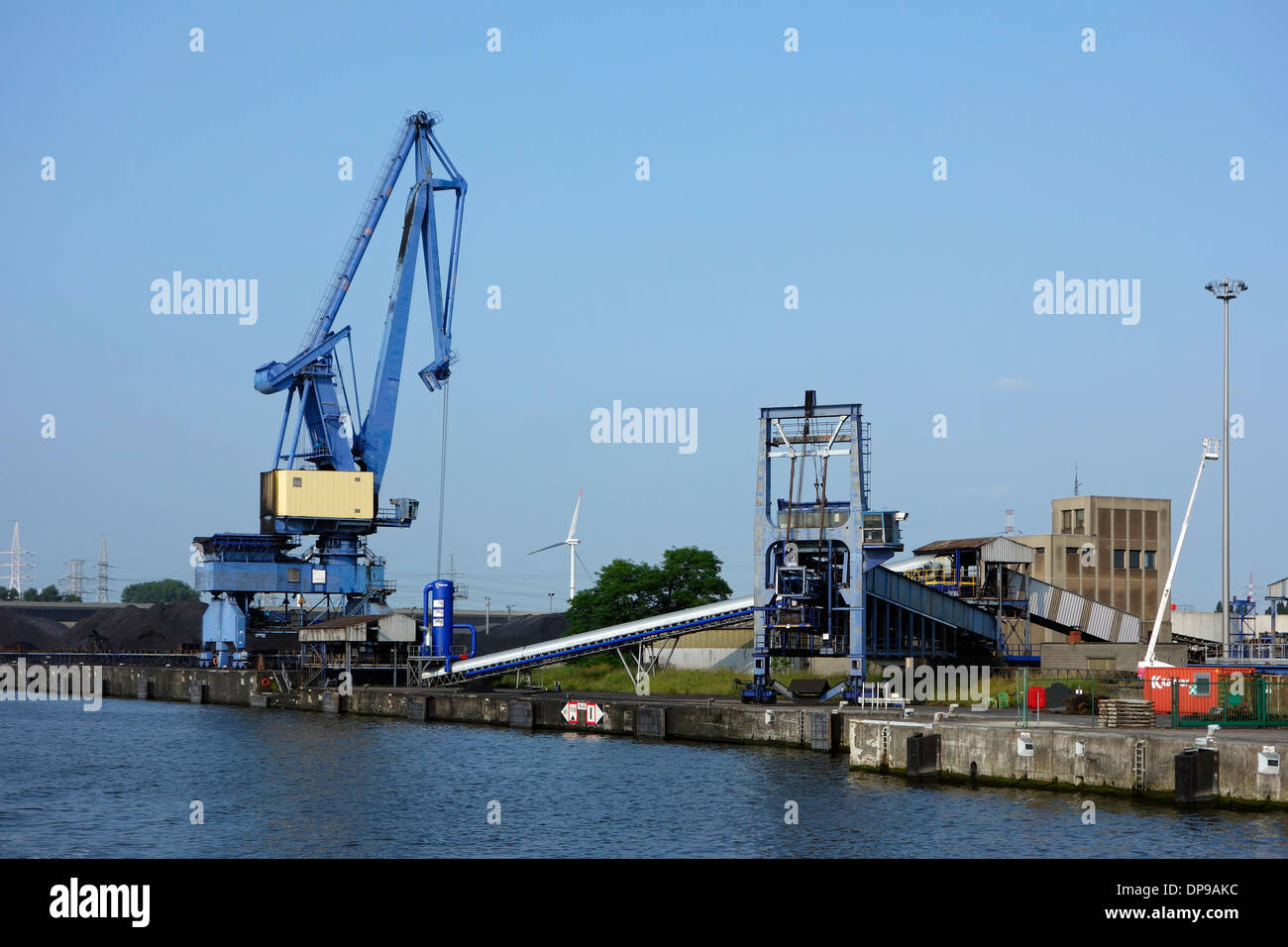 Dock crane and conveyor belt at SEA-invest / Ghent Coal Terminal / GCT at the port of Ghent, East Flanders, Belgium - Stock Image