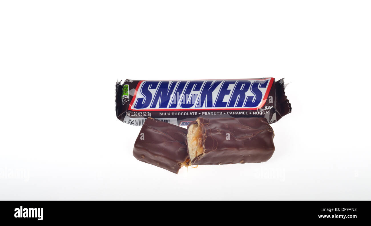 An opened Snickers bar with torn packaging  and candy outside in half showing filling, cutout USA - Stock Image