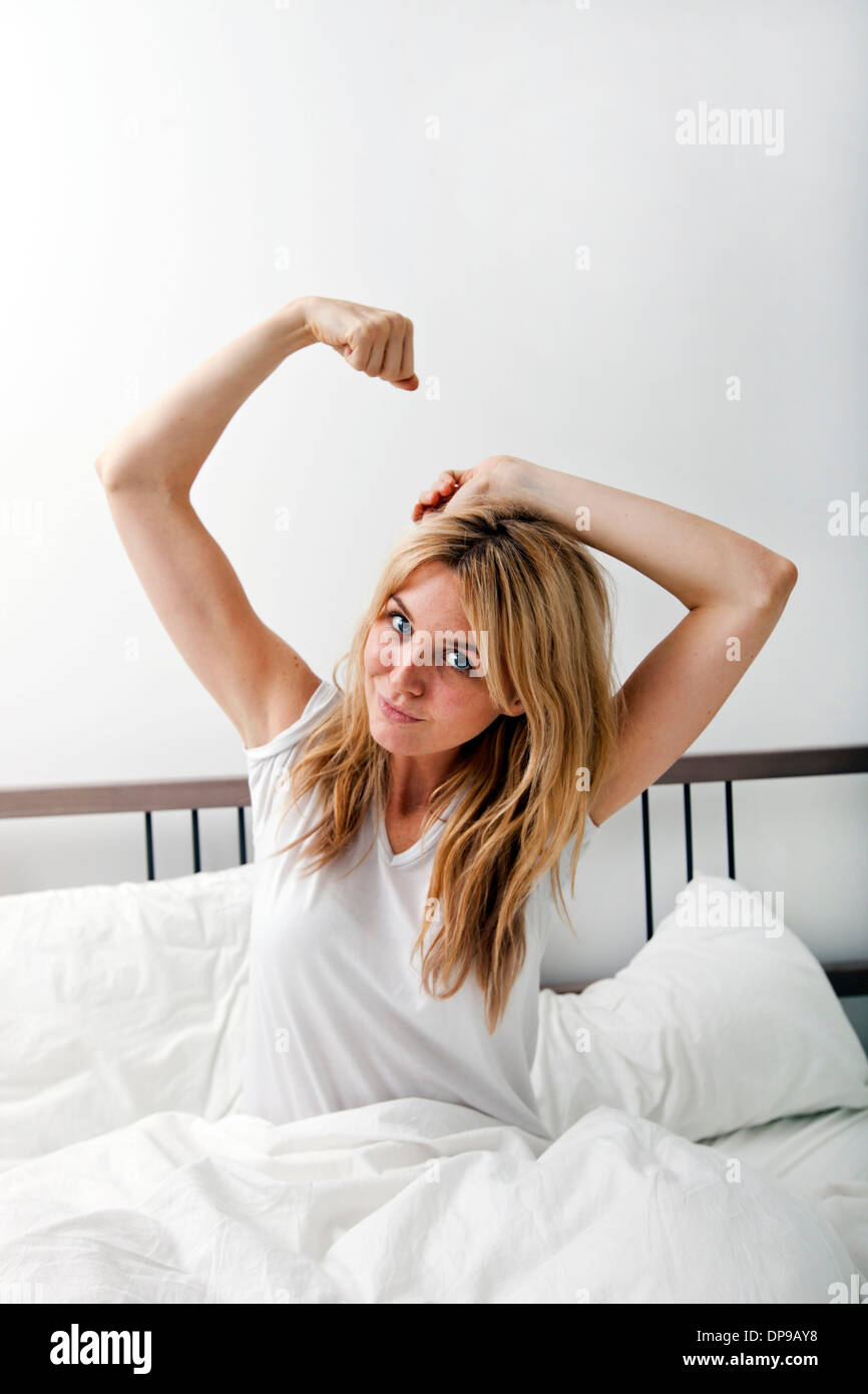 Portrait of young woman stretching in bed - Stock Image