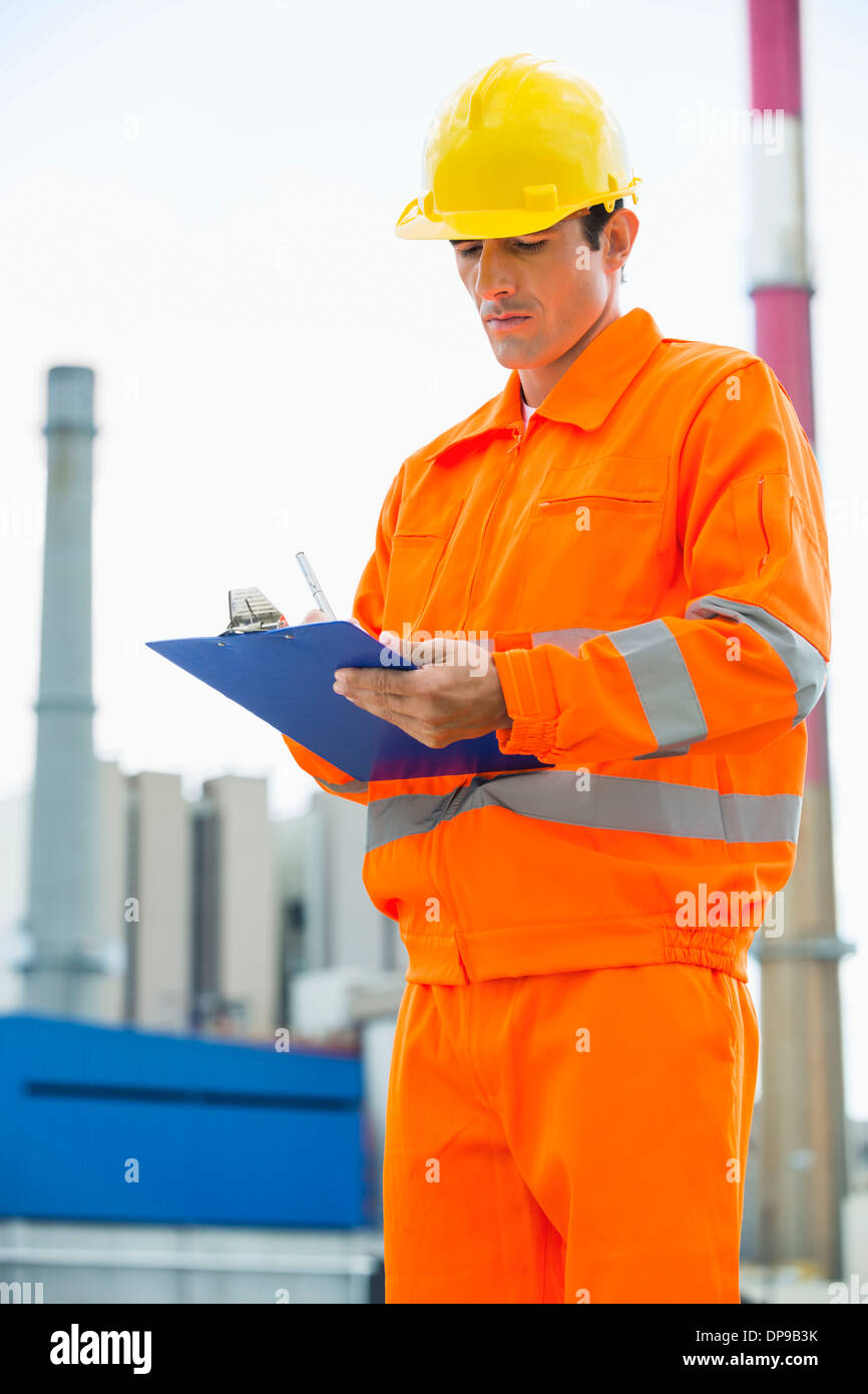 Male architect in protective workwear writing on clipboard at site - Stock Image