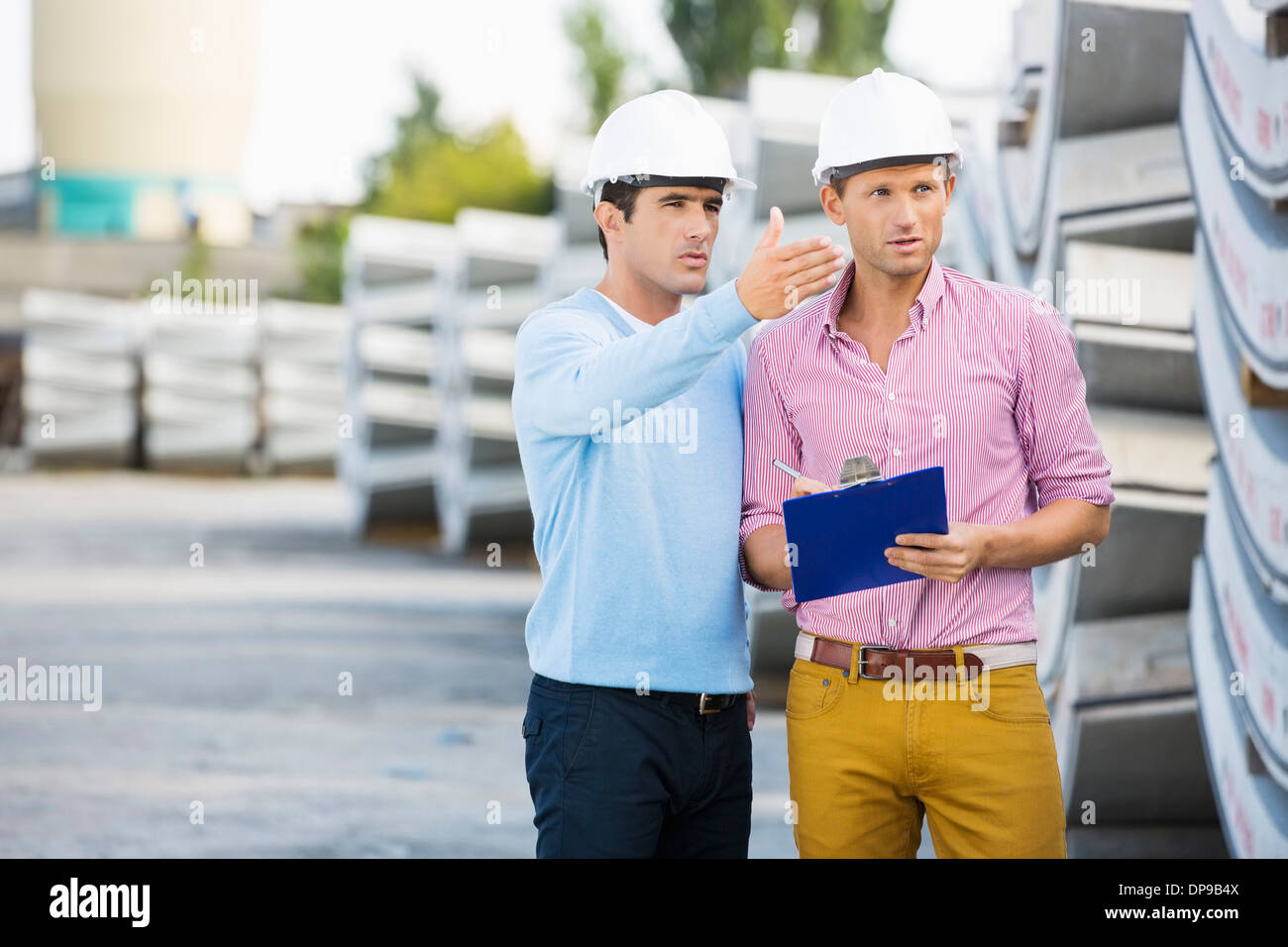 Male architects inspecting inventory at site - Stock Image