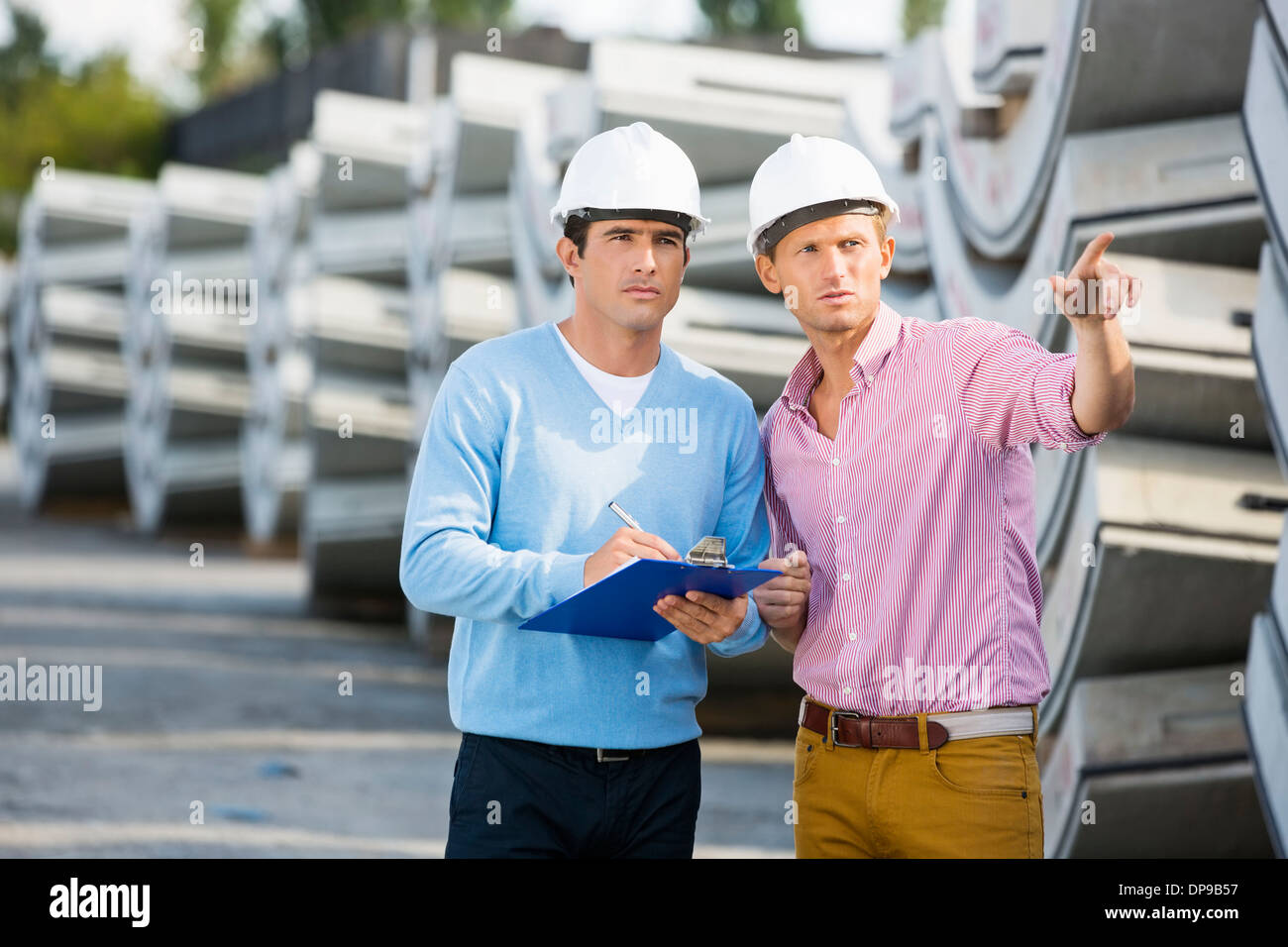 Architects inspecting stock at site - Stock Image