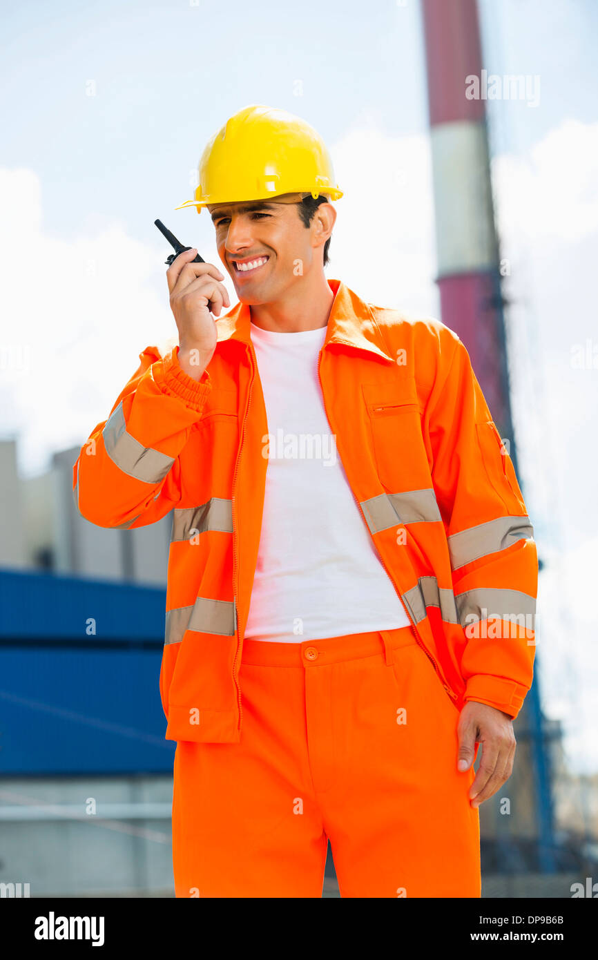 Happy architect wearing reflective workwear communicating on walkie-talkie at site - Stock Image