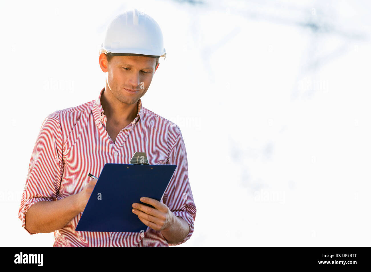 Male architect writing on clipboard at site - Stock Image