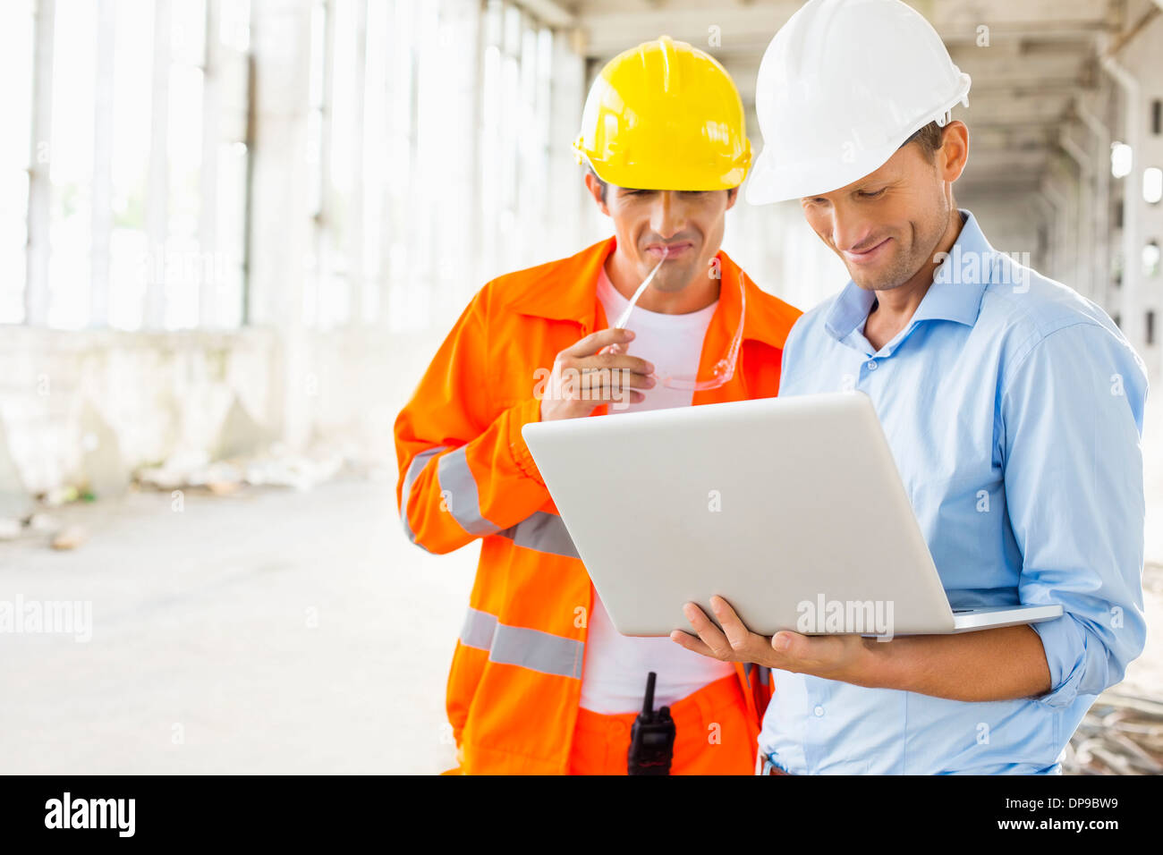 Male architects using laptop at construction site - Stock Image