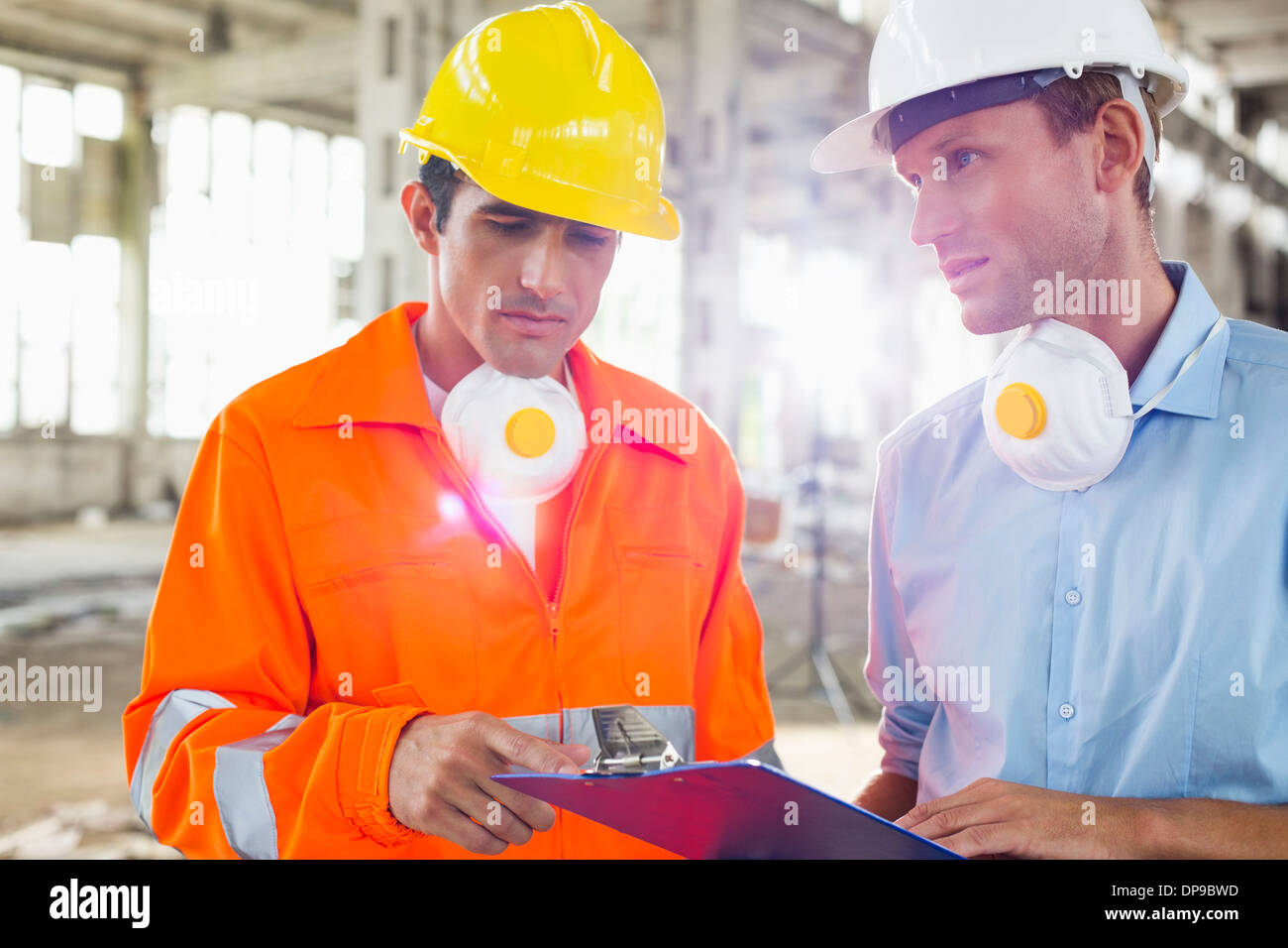 Male architects in protective workwear discussing at construction site - Stock Image