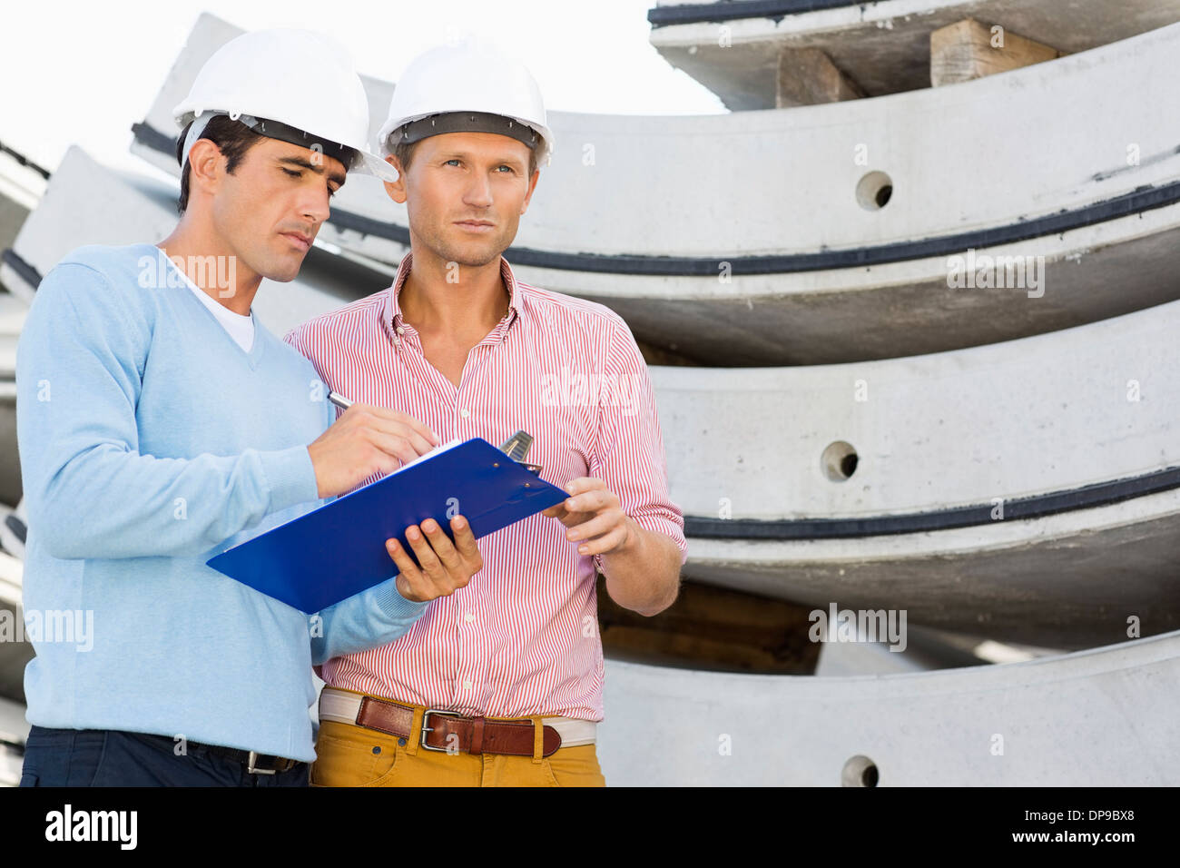 Architects with clipboard working at construction site - Stock Image