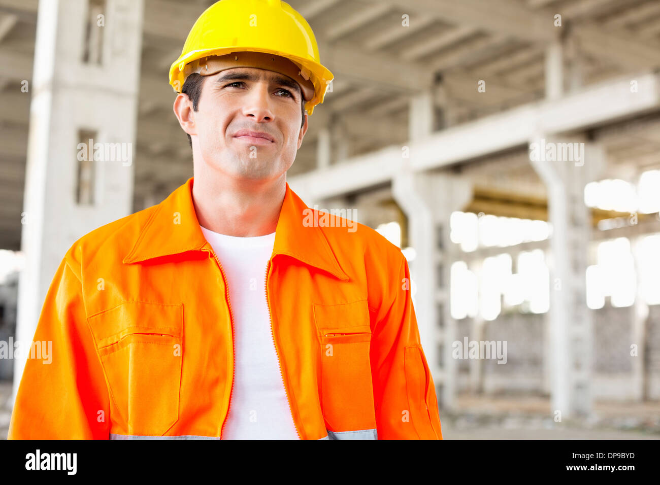 Handsome mid adult man wearing protective workwear at construction site - Stock Image