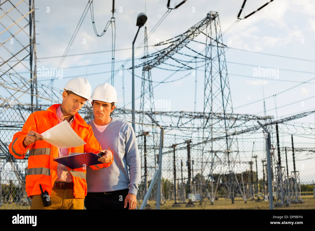 Male architects reviewing documents together at electric power plant - Stock Image