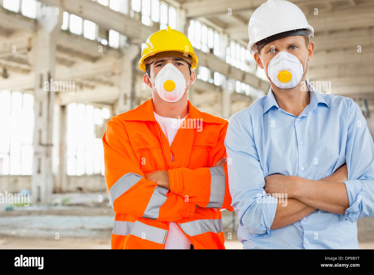 Portrait of confident male construction workers in protective workwear at site - Stock Image