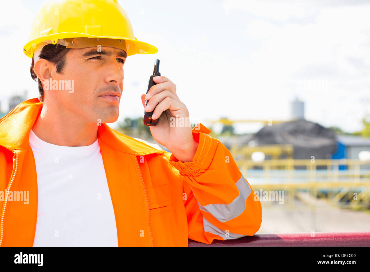 Male construction worker communicating on walkie-talkie at site - Stock Image
