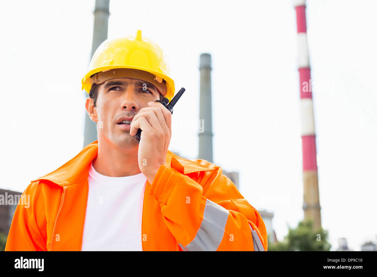 Male construction worker wearing reflective workwear communicating on walkie-talkie at site - Stock Image