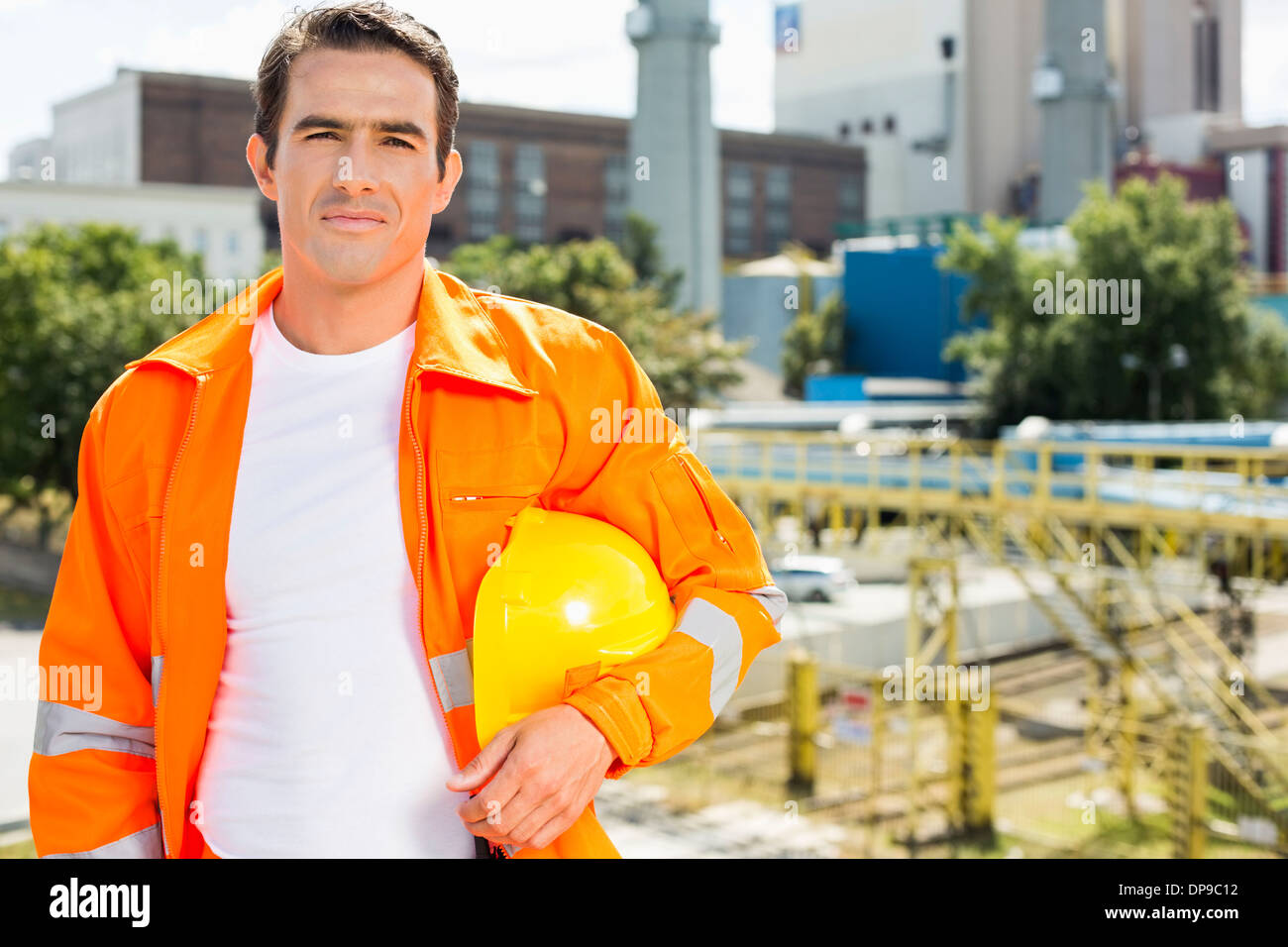 Portrait of male architect wearing reflective workwear at construction site - Stock Image