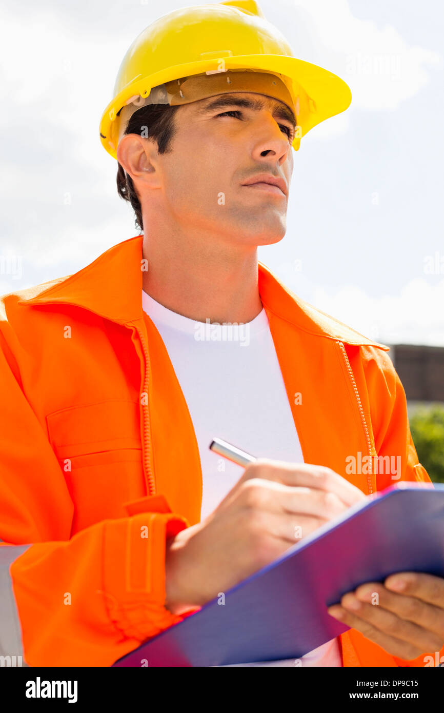 Male construction worker with clipboard looking away outside - Stock Image