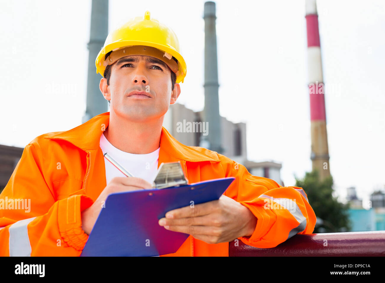 Male construction worker writing on clipboard at industry - Stock Image