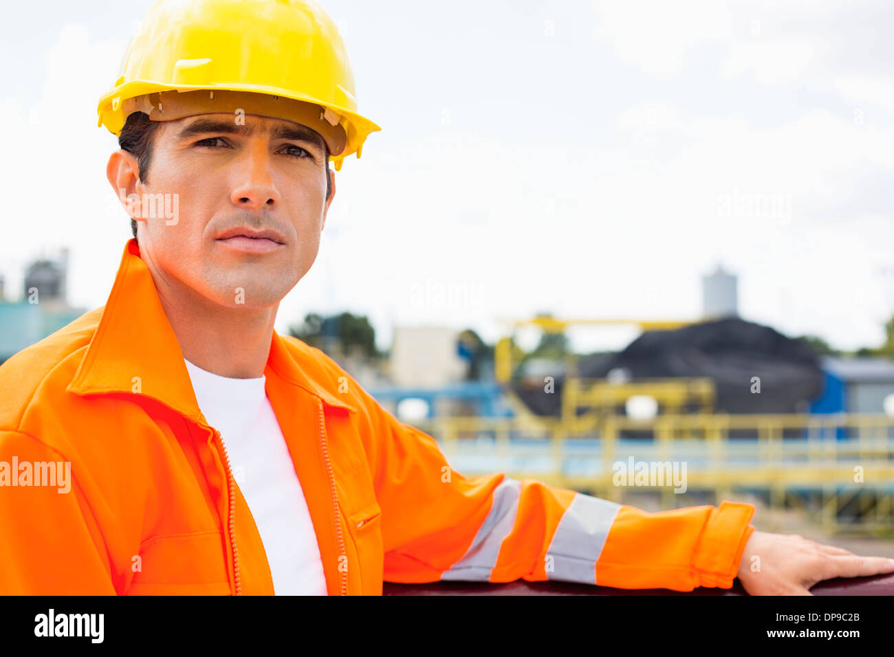 Portrait of handsome mid adult man wearing protective workwear at construction site - Stock Image