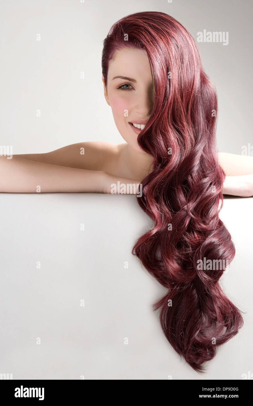 Beautiful woman with long red dyed hair against gray background - Stock Image