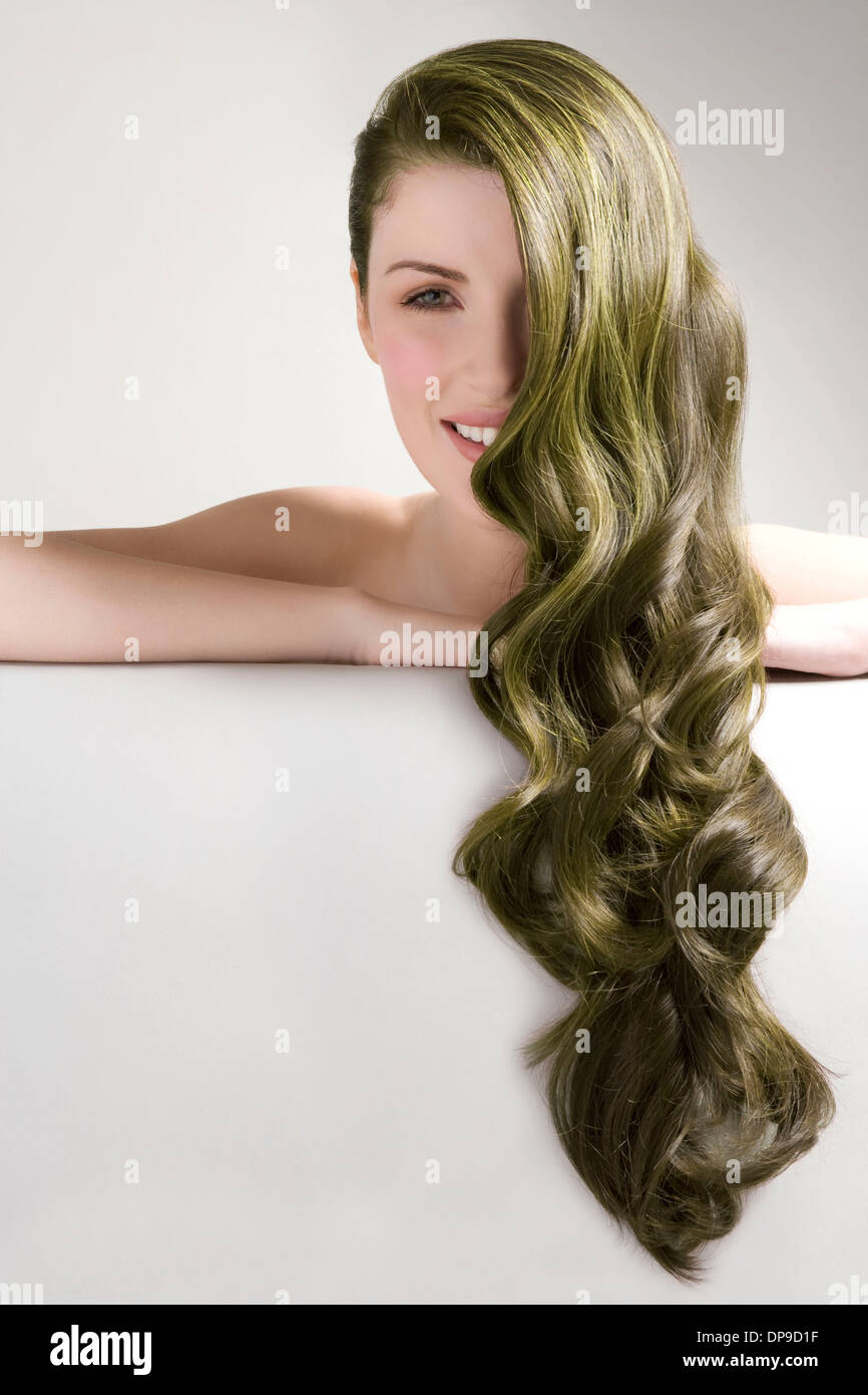 Beautiful woman with long green dyed hair against gray background - Stock Image