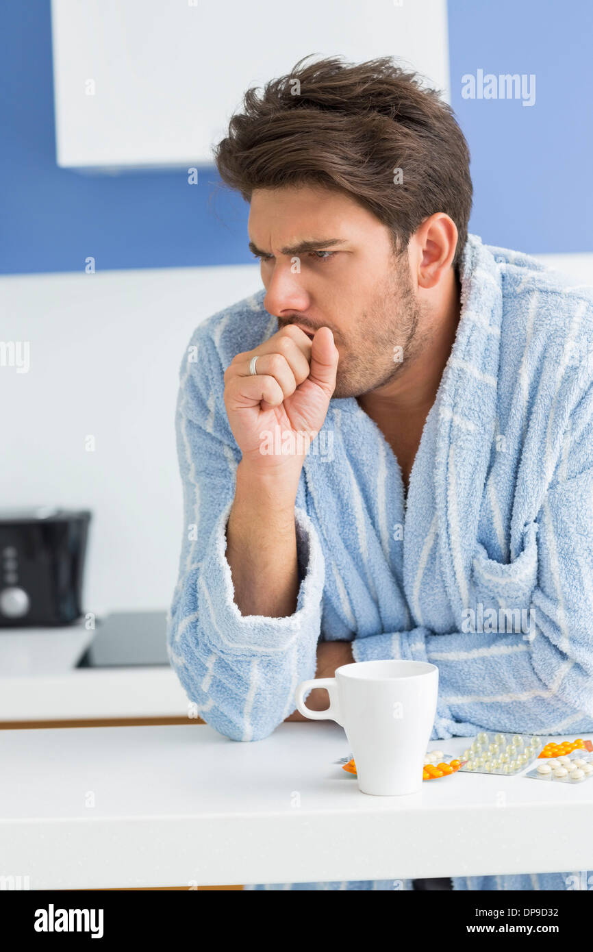 Young man coughing with coffee mug and medicine on kitchen counter - Stock Image