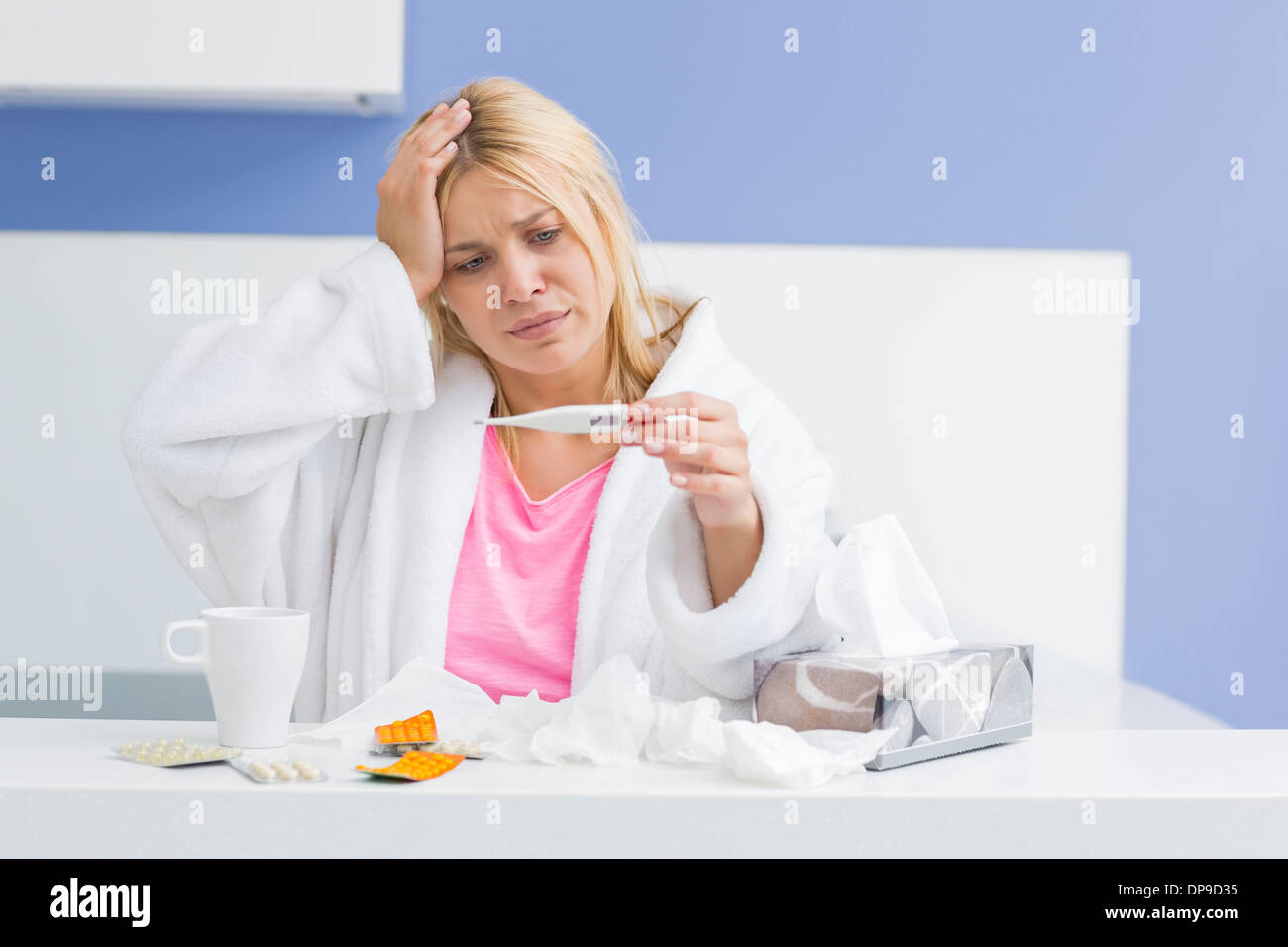 Young woman suffering from cold checking tempereature - Stock Image