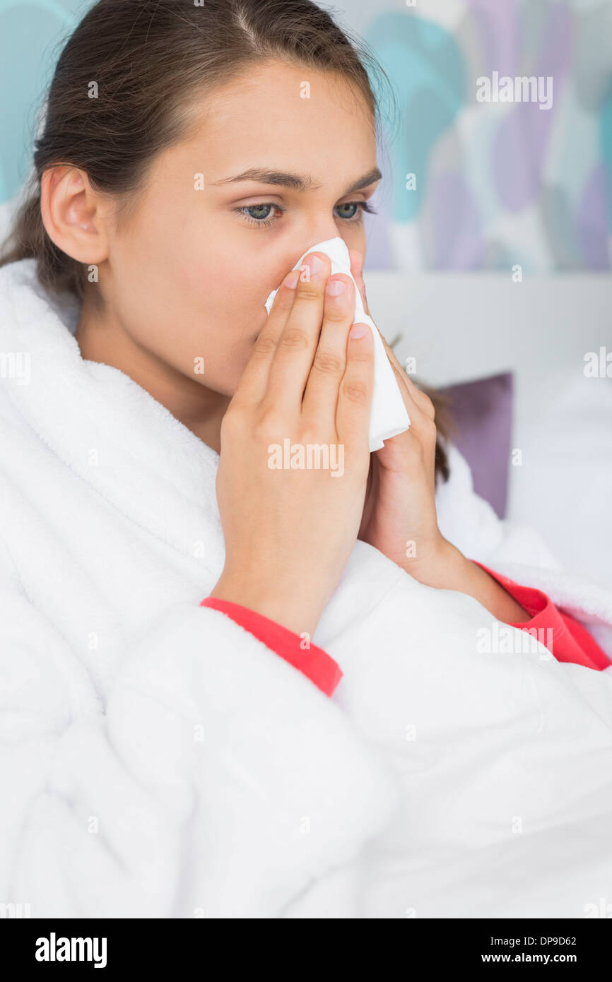 Young woman suffering from cold blowing nose in bedroom - Stock Image