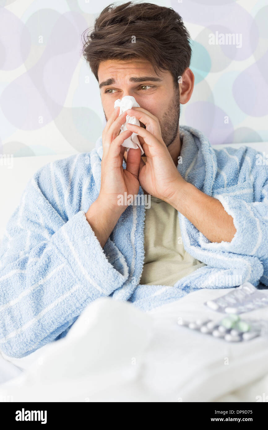 Sick man blowing his nose in tissue paper on bed at home - Stock Image