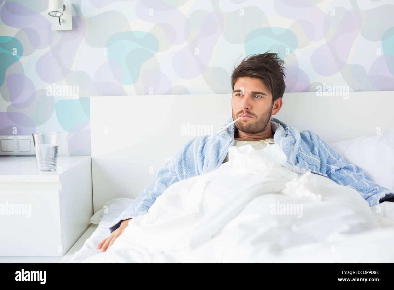 Sick man with thermometer in mouth reclining on bed at home - Stock Image